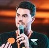 Foto Fellipe com um microfone dando uma palestra